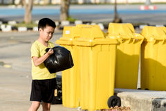 Boy carry garbage in bag for eliminate to the bin. Young Asian boy carry garbage in plastic bag for eliminate in the yellow bin under the sunlight Royalty Free Stock Photography