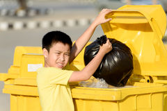 Boy carry garbage in bag for eliminate to the bin. Young Asian boy carry garbage in plastic bag for eliminate in the yellow bin under the sunlight Stock Photos