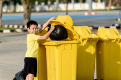 Boy carry garbage in bag for eliminate to the bin. Young Asian boy carry garbage in plastic bag for eliminate in the yellow bin under the sunlight Royalty Free Stock Photo