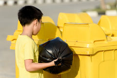 Boy carry garbage in bag for eliminate to the bin. Young Asian boy carry garbage in plastic bag for eliminate in the yellow bin under the sunlight Royalty Free Stock Images