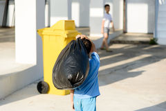 Boy carry garbage. Young Asian boy carry garbage in plastic bag for eliminate in the yellow bin under the sunligh Stock Image