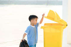 Boy carry garbage. Young Asian boy carry garbage in plastic bag for eliminate in the yellow bin under the sunligh Royalty Free Stock Photos