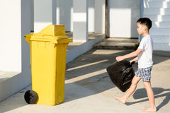 Boy carry garbage. Young Asian boy carry garbage in plastic bag for eliminate in the yellow bin under the sunligh Stock Photo