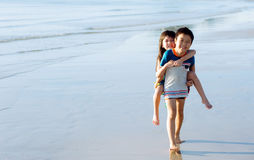 Boy carry his sister at his back Royalty Free Stock Images