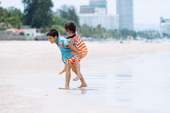 Boy carry his sister at his back Royalty Free Stock Photo