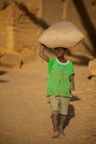 Boy carrying a bag of rice in the Dogon Land in Mali Royalty Free Stock Photos