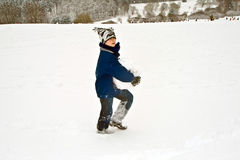Boy carrying a big snowball in wintry landscape Stock Photo