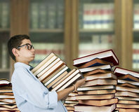Boy carrying books Royalty Free Stock Photos