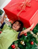 Boy carrying a Christmas present Stock Photography