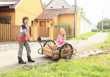 Boy carrying a girl on carriage. Little kids - boy carrying a girl kneeing on carriage Royalty Free Stock Photos