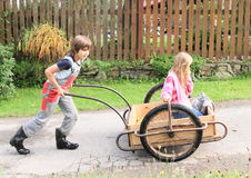 Boy carrying a girl on carriage. Little kids - boy carrying a girl kneeing on carriage Stock Photo