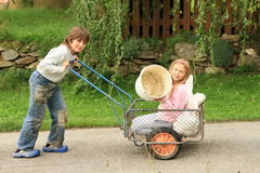 Boy carrying a girl on carriage. Little kids - boy carrying a girl kneeing on carriage and showing empty bucket Royalty Free Stock Photos