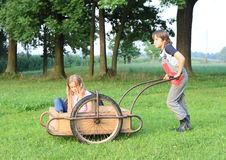 Boy carrying a girl on carriage Royalty Free Stock Image