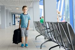 Boy carrying his luggage at airport Stock Images