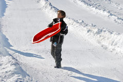 Boy Carrying His Sled Down the Hill. L with snow background Royalty Free Stock Photos