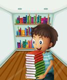 A boy carrying a pile of books Stock Photo