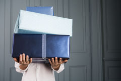 boy carrying pile of presents face obscured Royalty Free Stock Photo