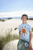 Boy Carrying Plastic Bag Filled With Garbage On Beach. Portrait of happy young boy carrying plastic bag filled with garbage on beach Royalty Free Stock Photo