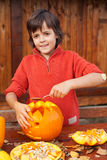 Boy carving his jack-o-lantern Stock Photos
