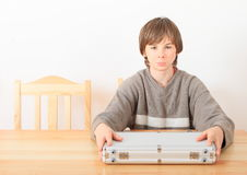 Boy with case for money. Little boy - seriouse kid sitting behind wooden table and holding case for money Stock Photography