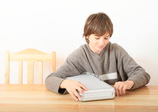 Boy with case for money. Little boy - smiling kid sitting behind wooden table and opening case for money royalty free stock photo
