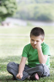 Boy in casual on grass leaning on fist Stock Images