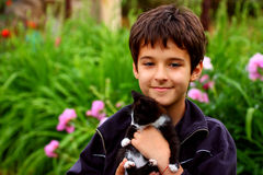 A boy with cat. A smiling boy holding in his hands small baby-cat outdoor on a blur, green background Stock Image
