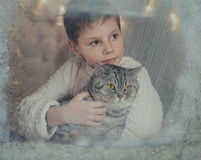A boy and a cat at a winter window. At the winter window frosty pattern on glass sits a boy in a knitted sweater with a cat Royalty Free Stock Photo