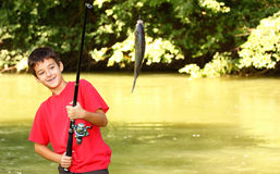 A boy catch a fish. On a river with fishing rod Royalty Free Stock Photo