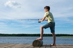 Boy catches fish with a fishing rod on a lake against the background of a beautiful sky, side view. Boy catches fish with a fishing rod on a lake against the royalty free stock images