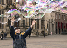 A boy catching big soap bubbles at the Bremen city center Stock Photography