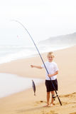 Boy catching fish. Little boy catching a big fish on beach stock images
