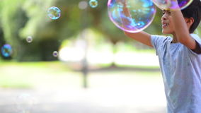 Boy Catching Soap Bubbles stock video footage