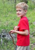 Boy catching wild snake stock photo