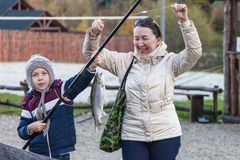 Boy caught trout, grandmother rejoices Royalty Free Stock Photography