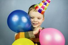Boy in a celebratory cap holding balloons Royalty Free Stock Photo
