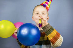 Boy in a celebratory cap holding balloons Royalty Free Stock Photography