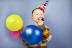 Boy in a celebratory cap holding balloons Stock Photography
