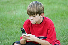 Boy on Cell. Boy playing game on cell phone Stock Image