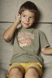 Boy with Cell Phone. A young boy listens to a cell phone while sitting on the couch. Vertical shot Royalty Free Stock Photos
