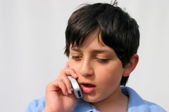 Boy On Cellphone. A boy chatting on his mobile phone Royalty Free Stock Photo