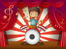 A boy at the center of the stage with a drum Royalty Free Stock Photography