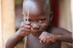 Boy at an ceremony in Benin. Young boy with stick at an Egungun ceremony in Cove, Benin, Africa royalty free stock images