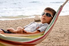 The boy is chafing away on a hammock by the sea royalty free stock photography