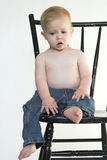 Boy on a Chair. Image of a cute toddler sitting on a black chair Royalty Free Stock Photo