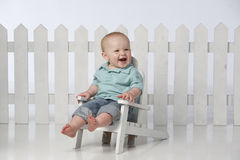 Boy in chair with fence Stock Photography