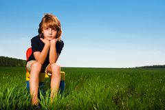 Boy on chair in field Royalty Free Stock Images