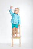 Boy on chair and pointing his finger up. Little boy standing on chair and pointing his finger up Stock Image