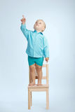 Boy on chair and pointing his finger up. Little boy standing on chair and pointing his finger up Stock Photo