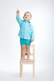 Boy on chair and pointing his finger up Stock Photography
